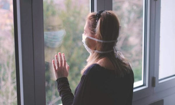 A woman with blond hair and wearing a COVID-19 face mask, has her hand on the glass. She has been living in isolation and looking at the outside world.